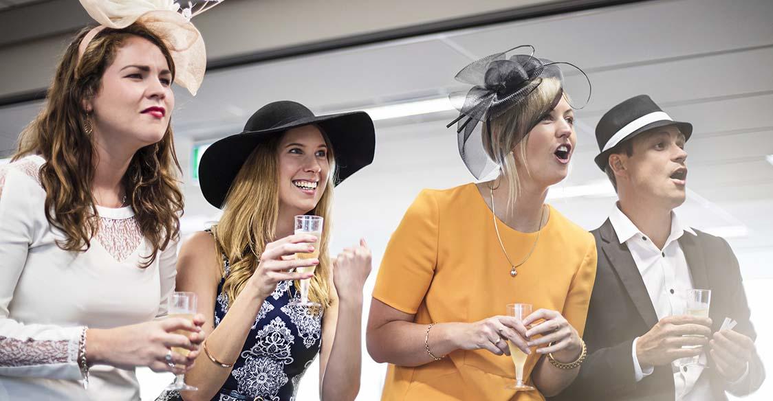 Women and a man watching a horse race